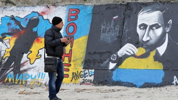 A man looks at a graffiti produced to support the territorial integrity of Ukraine. Pro-Russian protesters seized official buildings in the eastern cities of Kharkiv, Luhansk and Donetsk on Sunday night.