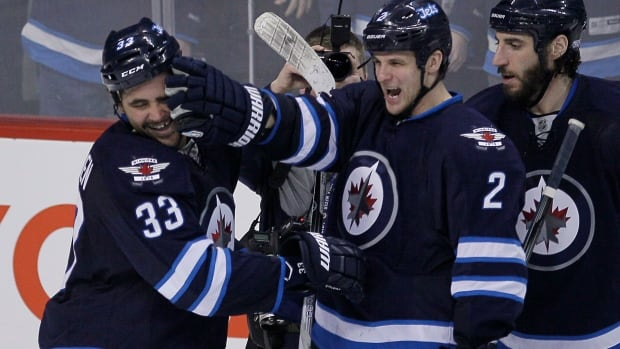 Winnipeg Jets' Dustin Byfuglien (33) and Adam Pardy (2) celebrate Byfuglien's overtime goal to beat the Toronto Maple Leafs 5-4 in Winnipeg on Jan. 25, 2014.