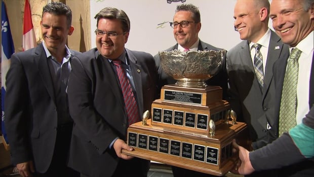 Montreal Mayor Denis Coderre (second from left) holds the Vanier Cup after announcing the championship game will be held in Montreal in November.