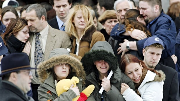 Family and friends of Brigitte Serre comfort each other after funeral services in Montreal Monday, Jan. 30, 2006. Serre, 17, was murdered while working her first overnight shift at a gas station in Montreal.