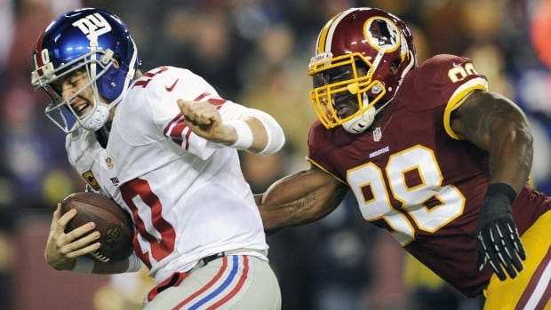New York Giants quarterback Eli Manning, left, is sacked by Washington Redskins outside linebacker Brian Orakpo during a Dec. 13, 2013 game.