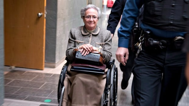 Former lieutenant governor Lise Thibault leaves a courtroom, escorted by courthouse security, Wednesday, March 26, 2014 in Quebec City.