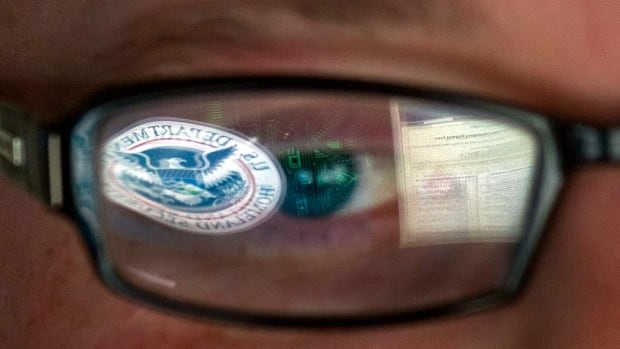 A reflection of the Department of Homeland Security logo is reflected in the glasses of a cybersecurity analyst. The department is asking organizations to report cyberattacks related to the Heartbleed bug.