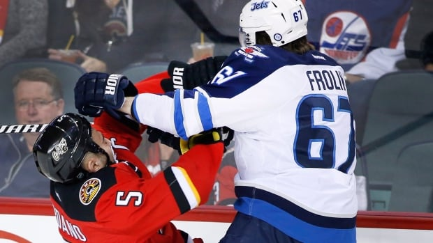 Winnipeg Jets' Michael Frolik, right, from Czech Republic, collides with Calgary Flames' Mark Giordano during first period of Calgary's last home game of the season.