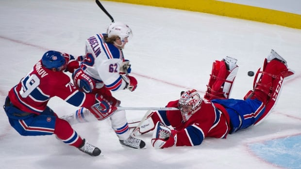 New York Rangers' Carl Hagelin, centre, slides in on Montreal Canadiens goaltender Carey Price, right, as Canadiens' Andrei Markov defends during third period NHL hockey action in Montreal on Saturday, Nov. 16, 2013.
