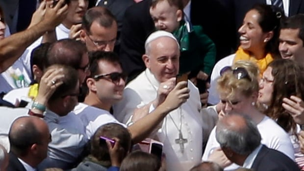 Pope Francis poses for pictures with faithful at the end of a Palm Sunday service in St. Peter's Square, at the Vatican, on Sunday.