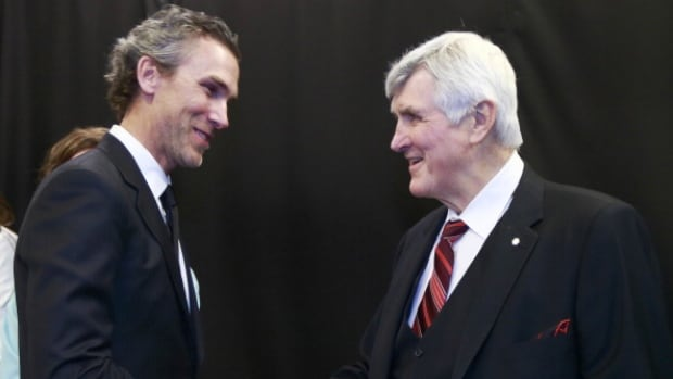 Pat Quinn, right, is congratulated by new Canucks' president of hockey operations Trevor Linden as the former coach was inducted into the organization's Ring of Honour Sunday night.