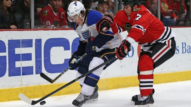 The Blackhawks' Sheldon Brookbank, right, and T.J. Oshie of the Blues move to the puck in an April 6 game in Chicago.