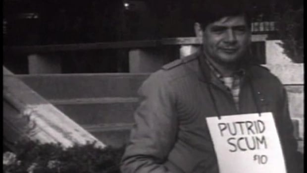 A still from the York University-produced documentary on Crad Kilodney's life shows the writer selling his books on the street with a sign around his neck.