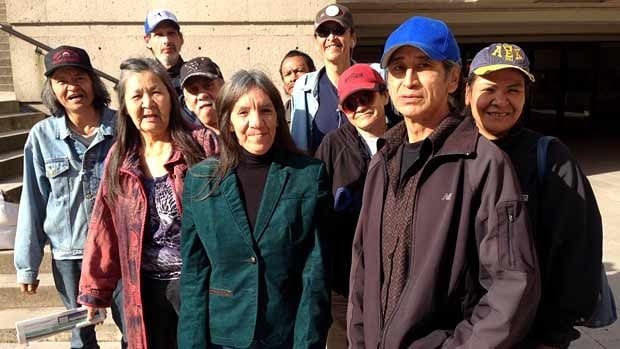 Defendant Ralph George, in the blue hat, stands next to co-defendents Susan Alec in green, and Loise Lagimodiere in red.