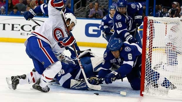 Brandon Prust of Montreal battles Tampa Bay in a 2013 game, with Lightning goalie Anders Lindback and defenceman Sami Salo also in view.