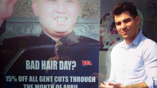 Barber Karim Nabbach of M&M Hair Academy stands next to a poster poking fun at North Korean leader Kim Jong-un's unusual hairstyle. North Korean diplomats have asked the British government to take action against the salon for displaying the poster.