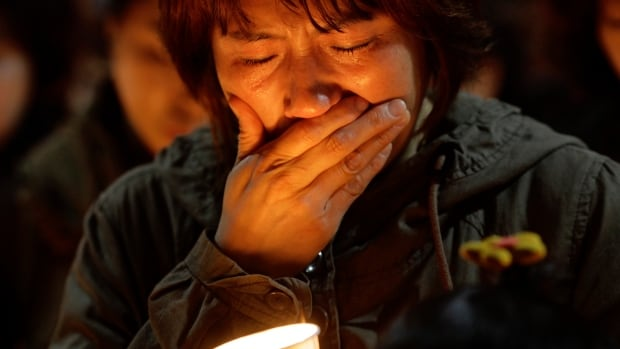 A woman offers prayers during a candlelight vigil for the missing passengers of a sunken ferry at Danwon High School in Ansan, South Korea, on Thursday.