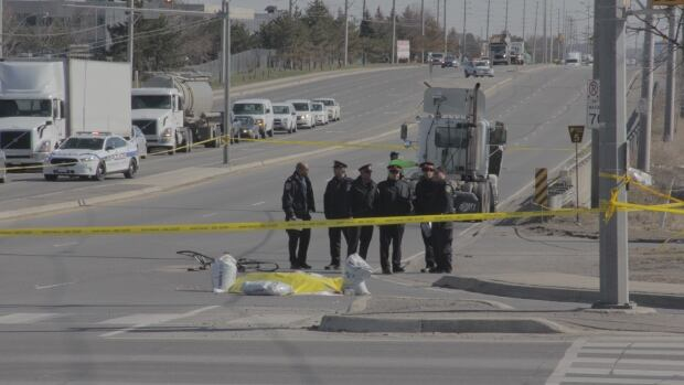 A mangled bicycle can be seen behind police tape and a gathering of officers.