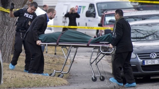 Police remove a body from the scene of a multiple fatal stabbing in northwest Calgary on Tuesday. First responders and police are being offered special support in the aftermath of the tragedy.