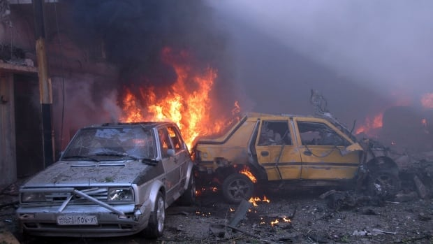 Cars burn after two car bombs in Homs exploded in April, killing 25 people and wounding more than 100.
