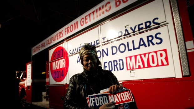 A women walks past an old City of Toronto fire truck as mayor Rob Ford gets ready to make his campaign launch in Toronto on Thursday, April 17, 2014.