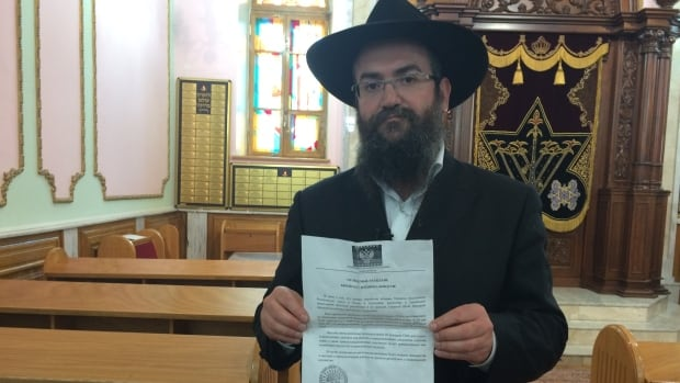 Rabbi Pinchas Vyshetsky at his synagogue in Donetsk, holding up one of the leaflets. About 50 flyers were handed out, as members of the Jewish community were leaving their synagogue after a service on the eve of Passover earlier this week.