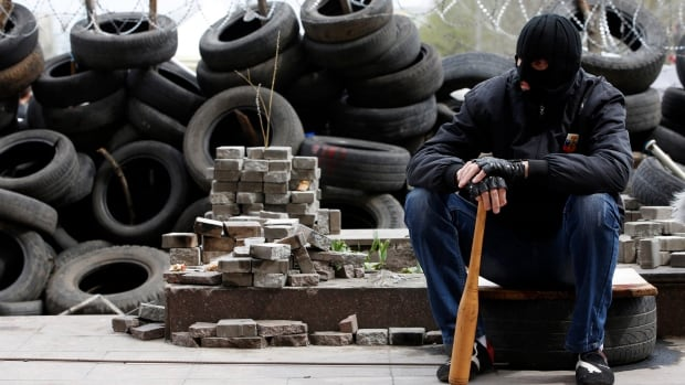 A pro-Russian protester wearing a balaclava and holding a baseball bat sits next to piles of bricks and tires outside a regional government building in Donetsk, eastern Ukraine, Saturday.