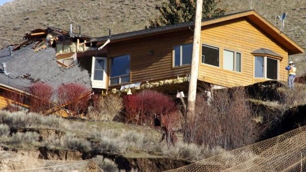 Workers can only watch helplessly as a slow-motion landslide spanning hundreds of yards splits a house in two and buckles concrete in the resort town of Jackson, Wyo.