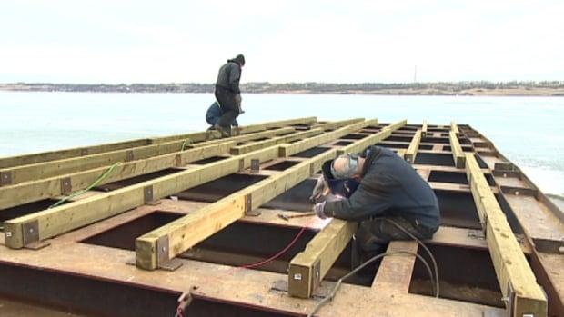 Volunteers work on rebuilding the pier at Regina Beach.