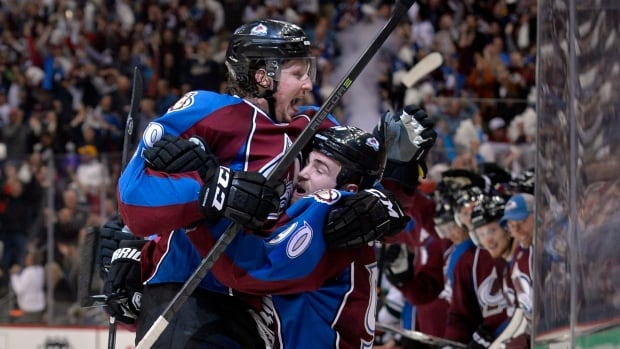 Colorado Avalanche center Ryan O'Reilly (90) is congratulated by teammate Nathan MacKinnon (29) after scoring a goal against the Minnesota Wild during the second period in Game 1 of an NHL hockey first-round playoff series on Thursday in Denver.