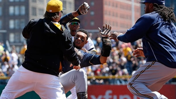 Pirates outfielder Travis Snider, left, takes down the Brewers' Carlos Gomez, middle, as Milwaukee's Rickie Weeks, right, joins a skirmish between the two teams during the third inning on April 20. On Wednesday, Gomez dropped his appeal and began serving a three-game suspension.