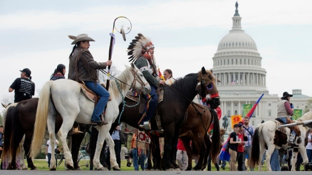 Shane Red Hawk of the Sioux Tribe from South Dakota, center, rides a horse with other Native Americans, farmers, ranchers and cowboys during the 'Reject and Protect' rally to protest against the Keystone XL pipeline on Tuesday.