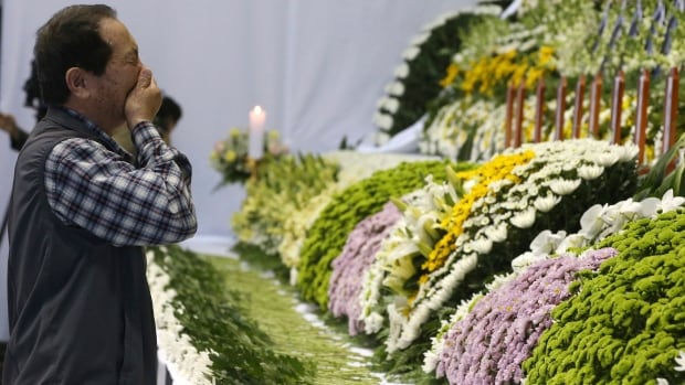 A mourner weeps as he pays tribute to the victims of the sunken ferry Sewol in the water off the southern coast at a gymnasium, in Ansan, South Korea, Wednesday.