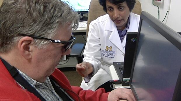 Dr. Naheed Khan works with Roger Pontz, left, on an exercise to test how well he sees shapes on a computer screen at the University of Michigan last week. Following an artificial implant, Pontz says he can walk through the house with ease.