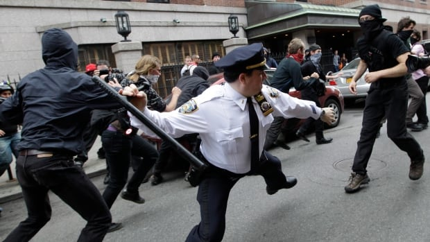 A New York City police officer swings a baton at Occupy Wall Street activists on May 1, 2012. This photo is among the many put on Twitter in response to the NYPD's request for Twitter users to share pictures of themselves posing with police officers. It likely wasn't what organizers of the social media campaign were expecting.