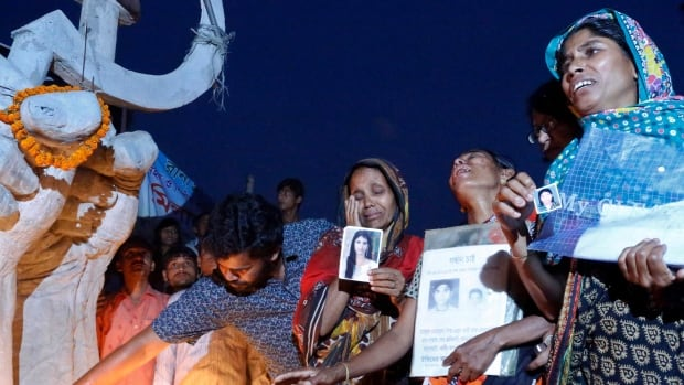 Relatives of victims of the Rana Plaza building collapse gather in front of a monument raised in memory of the victims.