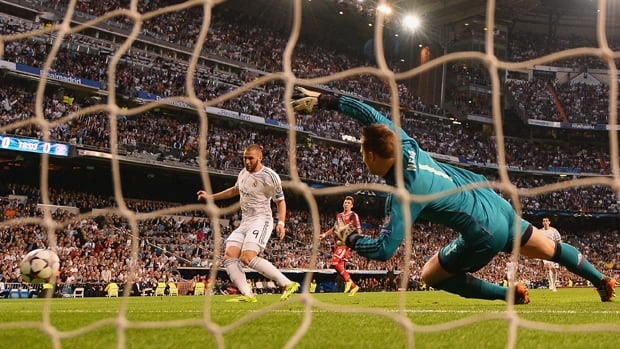 Karim Benzema (9) of Real Madrid scores on keeper Manuel Neuer in a 1-0 win over visiting Bayern Munich on Wednesday.