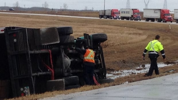 RCMP and emergency personnel at the scene of a semi-trailer rollover on the Highway 7 off-ramp at the north Perimeter Highway in Winnipeg on Thursday afternoon.