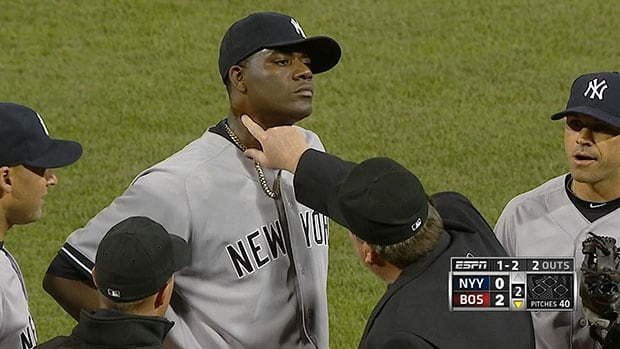 Umpire Gerry Davis touches the pine tar on Yankees pitcher Michael Pineda's neck during Wednesday's game at Fenway Park in Boston.
