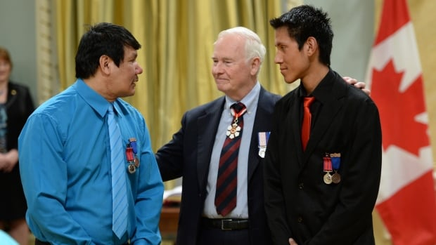 Governor General David Johnston presents the decoration of Bravery to Kelly Natomagan, left, and Logan Natomagan of Pinehouse Lake, Sask., during a ceremony at Rideau Hall in Ottawa Thursday. April 24, 2014.