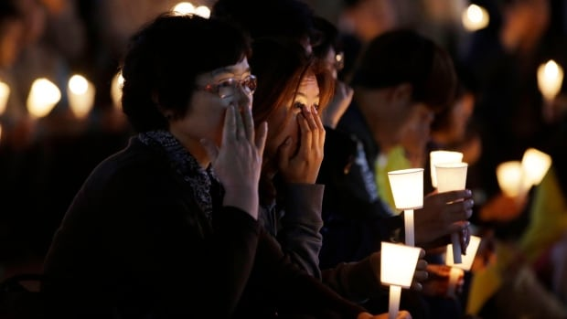 People hold candles during a vigil on Friday for the safe return of passengers of the sunken ferry Sewol in Ansan, South Korea.