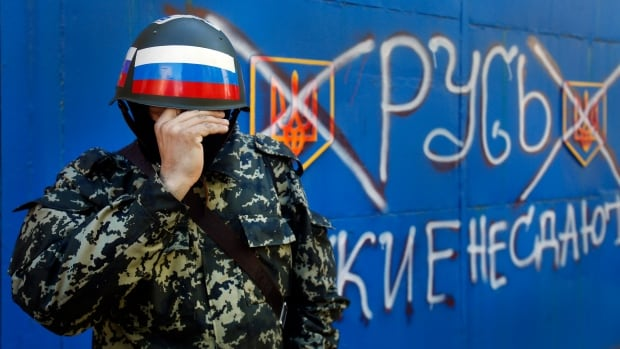 "A pro-Russian militant adjusts his mask in Slovyansk , eastern Ukraine, on Friday. The sign on the wall reading ""Russian do not surrender."""