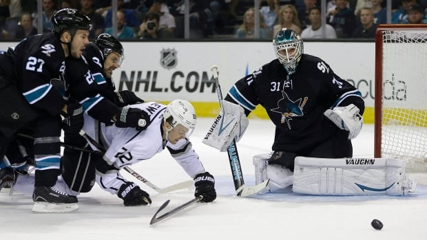 San Jose Sharks goalie Antti Niemi, right, eyes the puck as Los Angeles Kings' Trevor Lewis, centre, tangles with Sharks defenceman Scott Hannan (27) and Dan Boyle during the first period of Game 2 in San Jose.