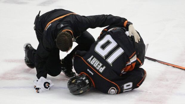 Anaheim Ducks forward Corey Perry is tended to by a trainer after he was hit by Dallas Stars forward Ryan Garbutt in the first period of Game 5.