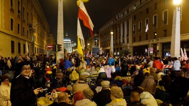 Pilgrims gather in via della Conciliazione, in front of St. Peter's Square, as they wait to attend the ceremony for the canonization of Pope John XXIII and Pope John Paul II, in Rome, early Sunday.