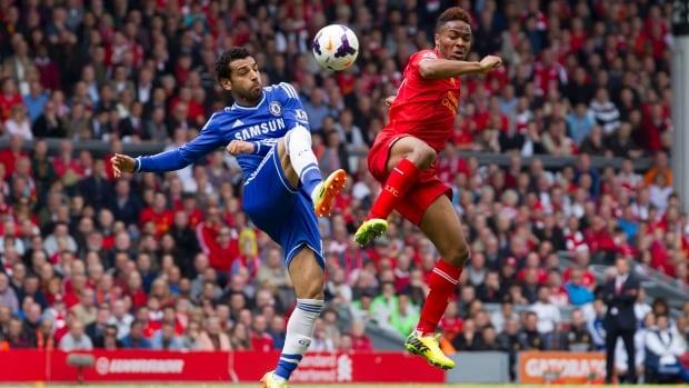 Liverpool's Raheem Sterling, right, fights for the ball against Chelsea's Mohammed Salah at Anfield Stadium on Sunday.