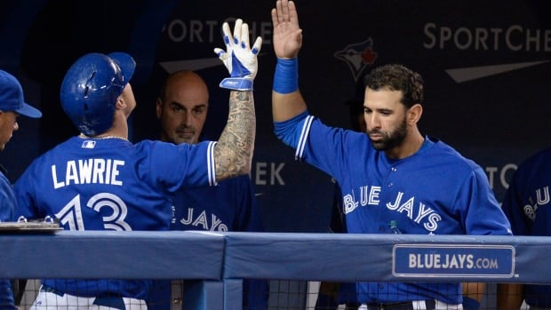 Toronto's Jose Bautista, from the Dominican Republic, congratulates Brett Lawrie on his solo homer against Boston on Sunday.