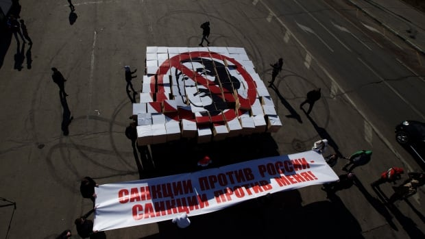 Protesters in Moscow hold up cardboard boxes with the portrait of U.S. President Barack Obama and a poster reading 'Sanctions against Russia - Sanctions against Me.'
