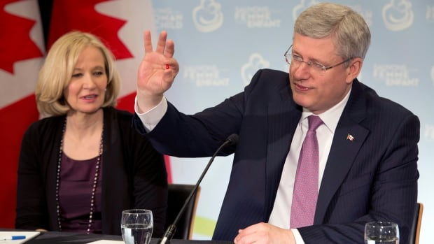 "Prime Minister Stephen Harper holds up a vitamin A pill as he and his wife Laureen participate in a round table for ""Saving Every Woman Every Child"" int Toronto on Monday, April 28, 2014."