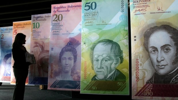 A woman looks at oversized versions of the Venezuelan currency, coined the 'Strong Bolivar,' in this 2007 photo in Caracas, Venezuela. Venezuelan students in Calgary say the country's state-run currency exchange is not transferring their tuition payments to the University of Calgary.