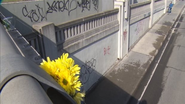 Flowers hang from the overpass above the spot where a cyclist was killed on Monday, after she was hit by a tractor trailer.