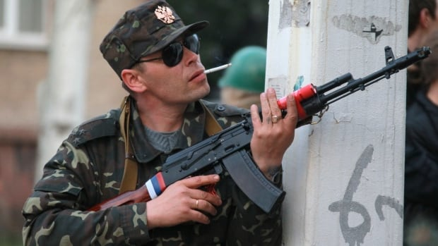 A pro-Russian gunman prepares his weapon as his comrades are about to storm a regional police station building in Luhansk, Ukraine — one of the largest cities in Ukraine's troubled east — on Tuesday as demonstrators demand greater autonomy for Ukraine's regions.