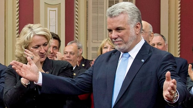Quebec Premier Philippe Couillard enjoys the warm embrace of his new cabinet, during the swearing in ceremony last week. Will the honeymoon last?