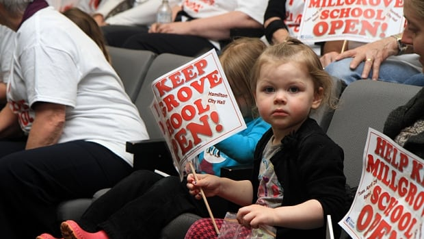 Zena Bainbridge, 2, holds a Millgrove sign at Hamilton city hall council chambers on Tuesday. Millgrove supporters packed the chambers for the public school board's public delegation night about West Flamborough schools.